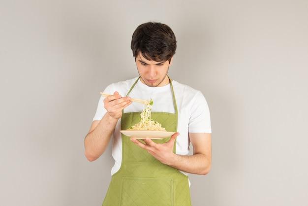 Porträt eines gutaussehenden mannmodells in der schürze, die einen teller mit essen hält.