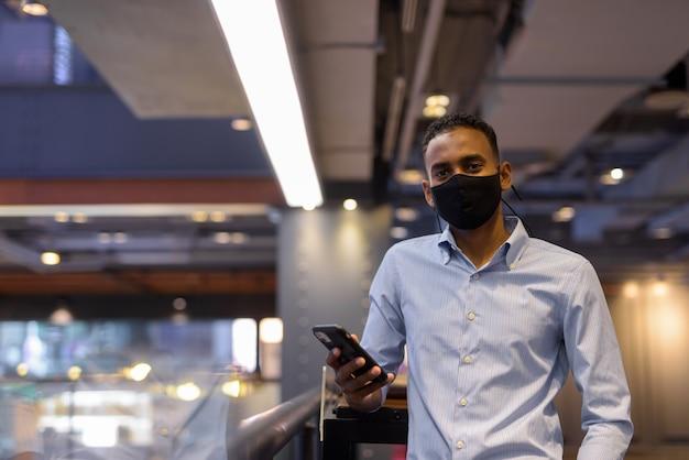 Porträt eines gutaussehenden schwarzafrikanischen geschäftsmannes im einkaufszentrum, der gesichtsmaske trägt und die horizontale aufnahme des mobiltelefons verwendet