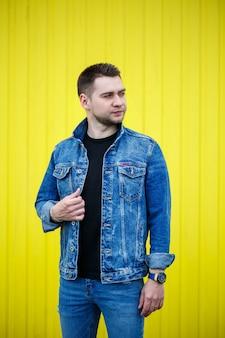 Porträt eines gutaussehenden, stilvollen mannes, ein mann in einem schwarzen, leeren t-shirt, der auf einem gelben wandhintergrund steht. urbaner kleidungsstil, modernes modisches bild. männermode