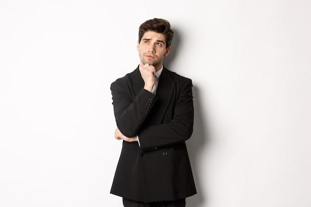 Porträt eines gutaussehenden und stilvollen mannes im anzug, der die obere linke ecke denkt und betrachtet, sich etwas über weihnachtsfeiertage vorstellt und auf weißem hintergrund steht.