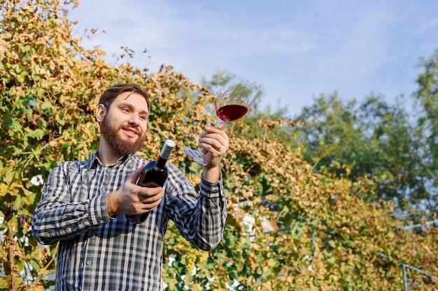 Porträt eines gutaussehenden winzers, der in seiner handflasche und ein glas rotwein hält und ihn probiert, die weinqualität überprüft, während er in den weinbergen steht. kleines unternehmen, hausgemachtes weinherstellungskonzept.