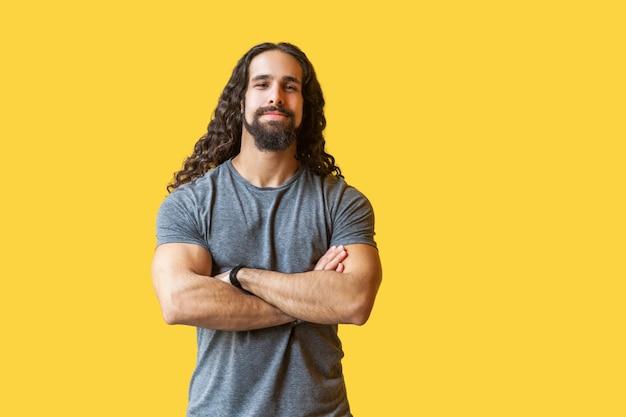 Porträt eines gutaussehenden, zufriedenen, bärtigen jungen mannes mit langen lockigen haaren in grauem t-shirt, der mit verschränkten armen steht und die kamera mit einem lächeln betrachtet. indoor-studioaufnahme auf gelbem hintergrund isoliert.