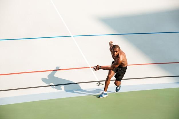 Porträt eines halbnackten gesunden sportlers, der anfängt zu laufen