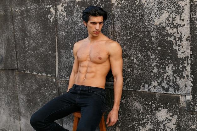 Porträt eines heißen, gesunden jungen mannes mit muskulösem körper und nacktem oberkörper, der six-pack-bauchmuskeln zeigt, die an der alten schwarzen wand aufwerfen.