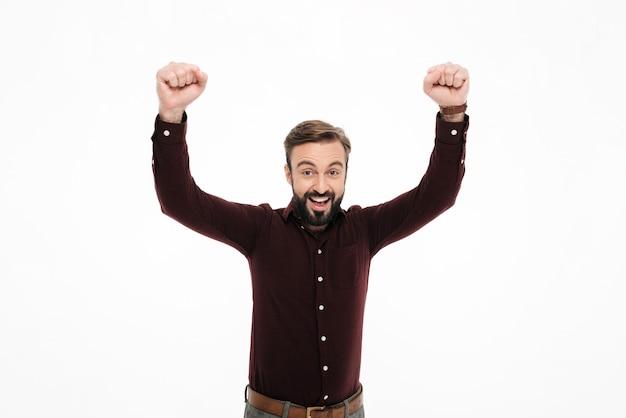 Porträt eines heitren glücklichen mannes, der erfolg feiert