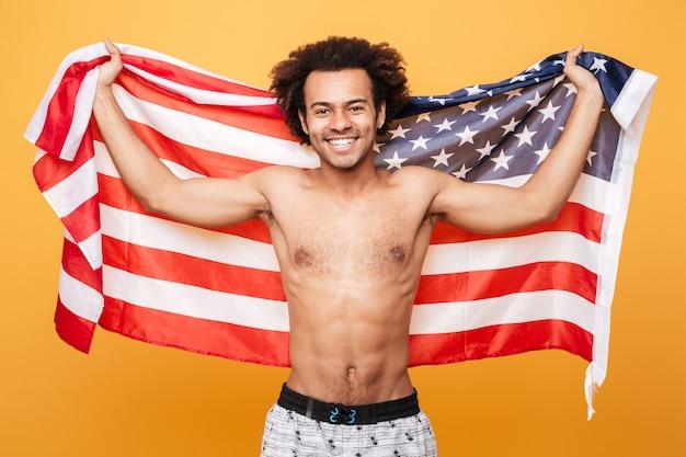 Porträt eines hemdlosen afroamerikanischen mannes, der usa-flagge hält