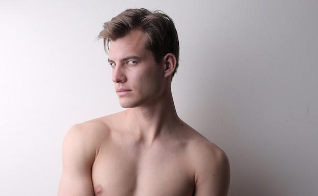 Porträt eines hemdlosen jungen mannes, der gegen eine weiße wand steht