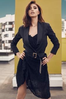 Porträt eines herrlichen hellen kleides der brunettefrau in mode, das auf dem dach eines gebäudes aufwirft