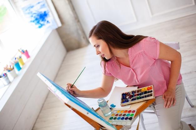 Porträt eines herrlichen weiblichen künstlers, der an einigen kunstprojekten auf ihrem studio arbeitet