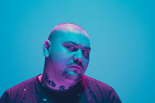 Porträt eines hipster-typs mit buntem neonlicht an blauer wand. männliches model mit ruhiger und ernster stimmung.