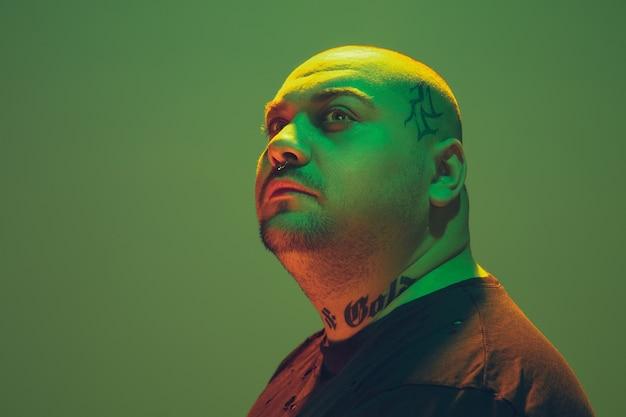 Porträt eines hipster-typs mit buntem neonlicht auf grüner wand. männliches model mit ruhiger und ernster stimmung.