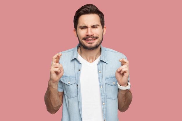 Porträt eines hoffnungsvollen, gutaussehenden, bärtigen jungen mannes im blauen hemd im casual-stil, der mit gekreuzten fingern, geschlossenen augen und hoffnung auf den sieg steht. indoor-studioaufnahme, isoliert auf rosa hintergrund.