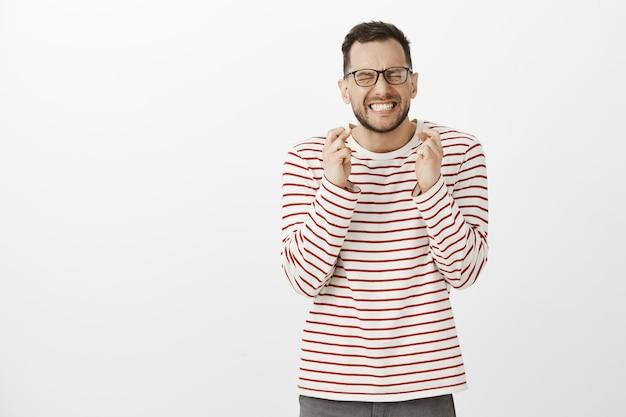 Porträt eines hoffnungsvollen gutaussehenden männlichen models in einer schwarzen, trendigen brille, geballten fäusten und schließenden augen, während sie die daumen drücken und gott betteln, beten oder sich wünschen, nervös sein und gewinnen wollen