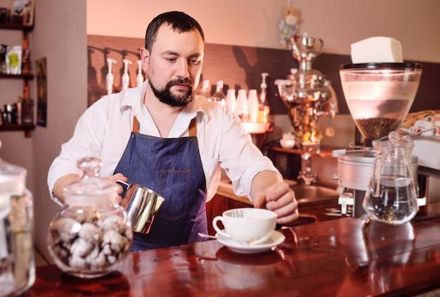Porträt eines hübschen bärtigen barista, das kaffee auf dem hintergrund eines kaffeehauses zubereitet