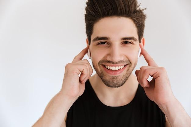 Porträt eines hübschen fröhlichen lächelnden glücklichen jungen sportsmannes lokalisiert über hörender musik der weißen wand mit kopfhörern.