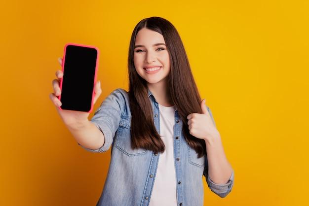 Porträt eines hübschen, fröhlichen mädchens, das in den händen hält, zeigt den leeren raum des touchscreens an, hebt den daumen hoch