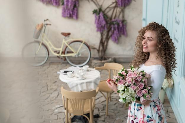 Porträt eines hübschen gelockten mädchens streichelt einen blumenstrauß von den rosen, die im straßencafé stehen und gerade bild schauen