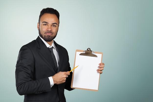 Porträt eines hübschen geschäftsmannes des schwarzen mannes, der ein klemmbrett hält