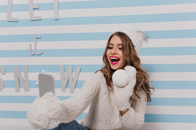 Porträt eines hübschen, gut aussehenden slawischen modells, das mit schneeball in ihren händen aufwirft. mädchen mit dunkelblonden haaren in gestrickten handschuhen macht selfie