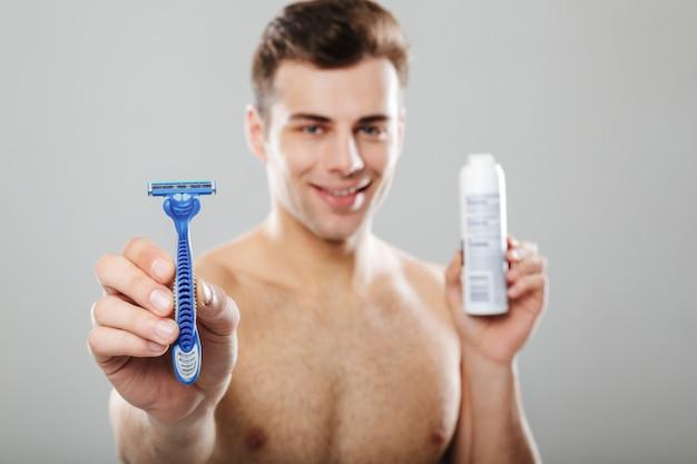 Porträt eines hübschen halben nackters, der rasiermesser zeigt