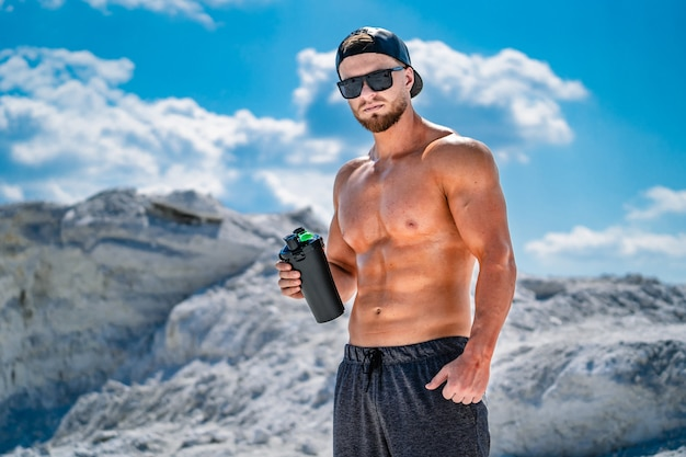 Porträt eines hübschen halbnackten bodybuilders. brille und mütze auf. sportflasche wasser in den händen.