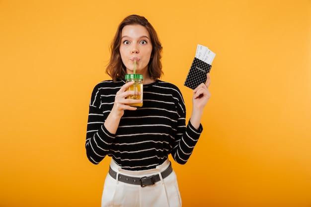 Porträt eines hübschen haltenen passes und des trinkenden cocktails