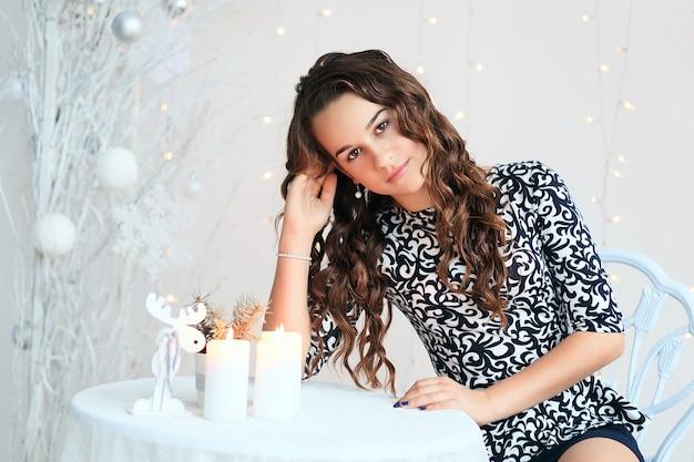 Porträt eines hübschen jugendlich mädchens mit fließendem langem lockigem haar im innenraum mit weihnachtsdekorationen