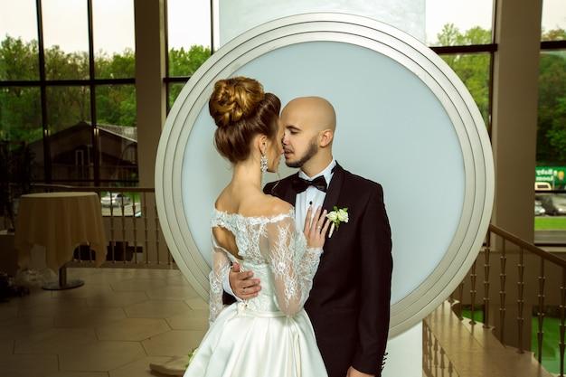 Porträt eines hübschen jungen, gerade verheirateten paares, das sich verliebt und einander ansieht