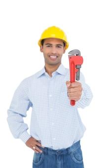 Porträt eines hübschen jungen heimwerkers, der rohrschlüssel hält