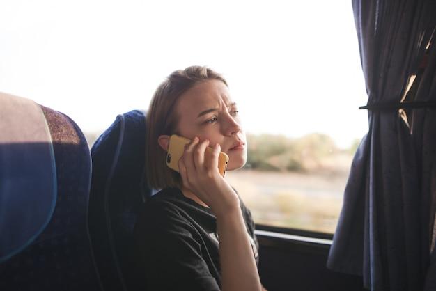 Porträt eines hübschen jungen mädchens, das in einem bus sitzt und am telefon spricht
