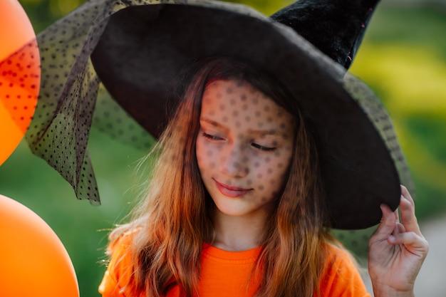 Porträt eines hübschen jungen mädchens mit orangefarbenen halloween-ballons, schwarzem hut und hemd, das auf der straße posiert. der fokus liegt auf den haaren. halloween-konzept.