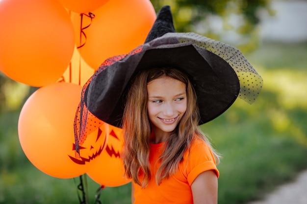 Porträt eines hübschen jungen mädchens mit orangefarbenen halloween-ballons, schwarzem hut und hemd, das auf der straße posiert. halloween-konzept.
