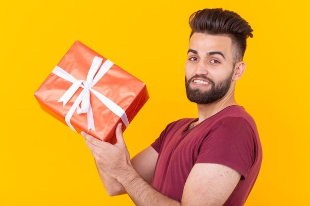Porträt eines hübschen jungen männlichen hipsters mit einem bart, der auf einer gelben wand aufwirft und a hält