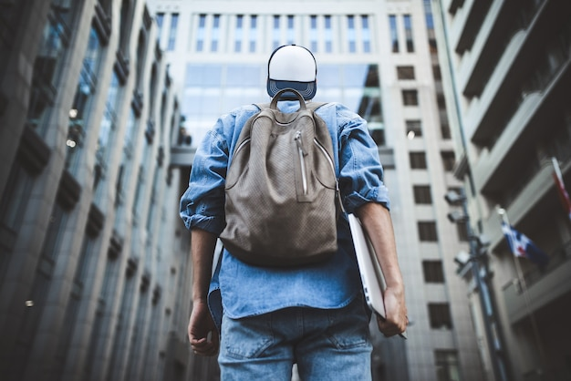 Porträt eines hübschen jungen männlichen studenten mit rucksack, der am gebäudehintergrund auf der straße steht