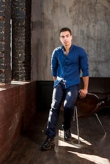Porträt eines hübschen jungen mannes, der auf stuhl in einem raum sich lehnt