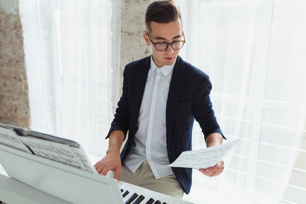 Porträt eines hübschen jungen mannes, der das musikalische blatt spielt klavier spielt