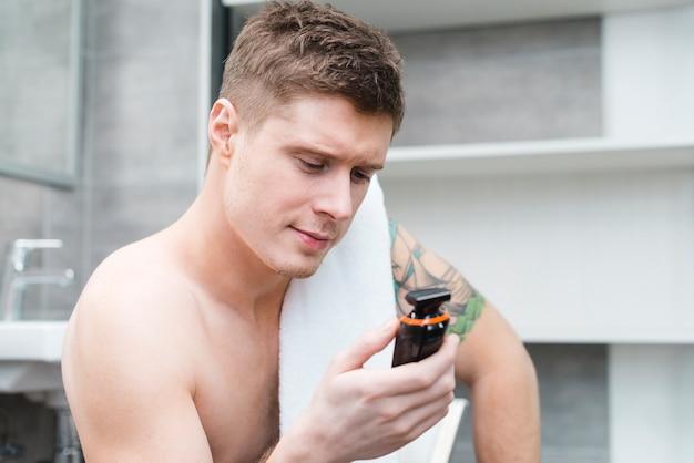 Porträt eines hübschen jungen mannes, der elektrorasierer im badezimmer betrachtet