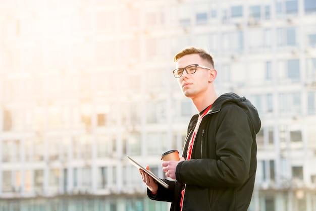 Porträt eines hübschen jungen mannes, der in der hand digitale tabletten- und mitnehmerkaffeetasse hält