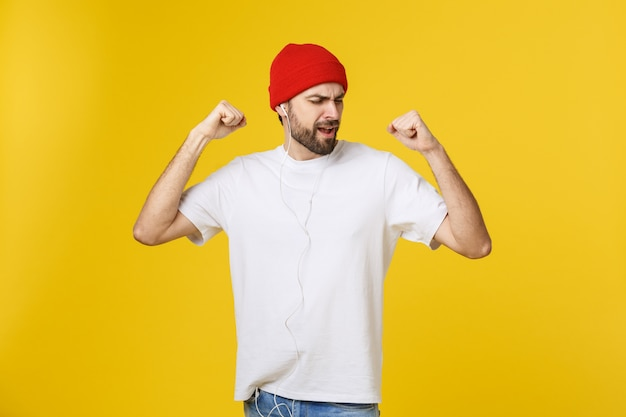 Porträt eines hübschen jungen mannes, der musik tanzt und hört, lokalisiert auf gelbem raum