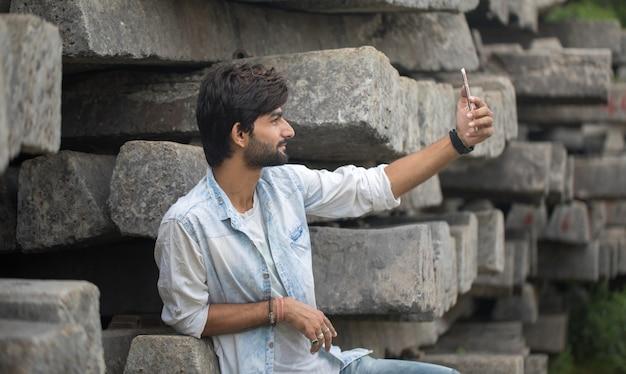 Porträt eines hübschen jungen mannes, der selfie auf handy im freien nimmt
