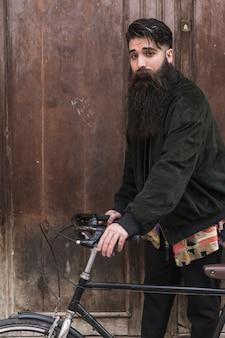 Porträt eines hübschen jungen mannes mit dem langen bart, der mit seinem fahrrad steht
