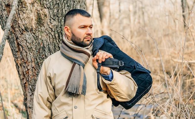Porträt eines hübschen jungen mannes mit einem bart, der draußen hängt.