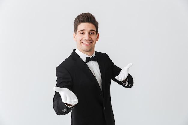 Porträt eines hübschen jungen mannkellners, der smoking und handschuhe trägt, die lokal über weißer wand stehen