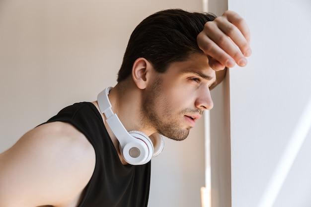 Porträt eines hübschen jungen sportlers, der in der nähe des fensters mit kopfhörern am hals steht.