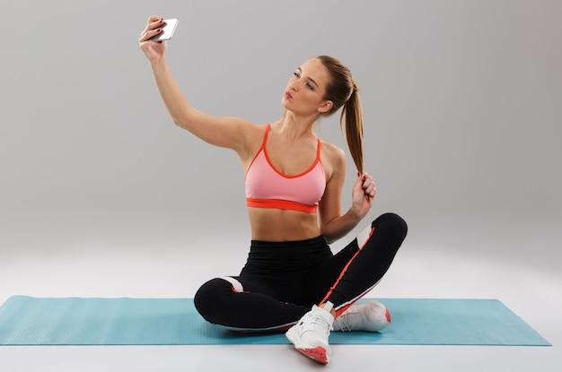 Porträt eines hübschen jungen sportmädchens, das selfie nimmt
