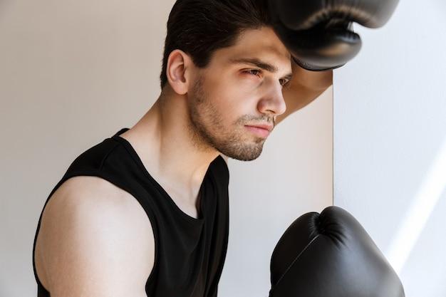 Porträt eines hübschen jungen sportmannboxers in den handschuhen, die nahe fenster stehen.