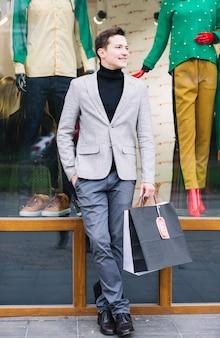 Porträt eines hübschen kerls, der in der hand einkaufstaschen hält, die vor fensteranzeige stehen