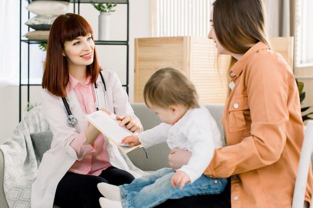 Porträt eines hübschen kinderarztes, der die behandlung für junge mutter und ihr baby erklärt, arztbesuch zu hause