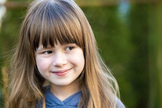 Porträt eines hübschen kindermädchens mit grauen augen und langen blonden haaren, das draußen lächelt