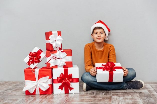 Porträt eines hübschen kleinen jungen in weihnachtsmann-hut, der geschenkbox sitzt und hält